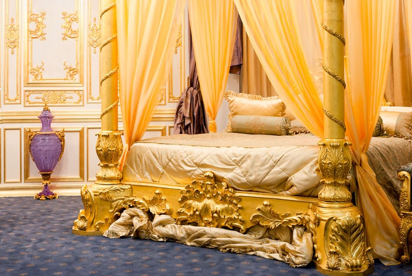 Beautiful four post bed with gold drapery and gilded bed frame