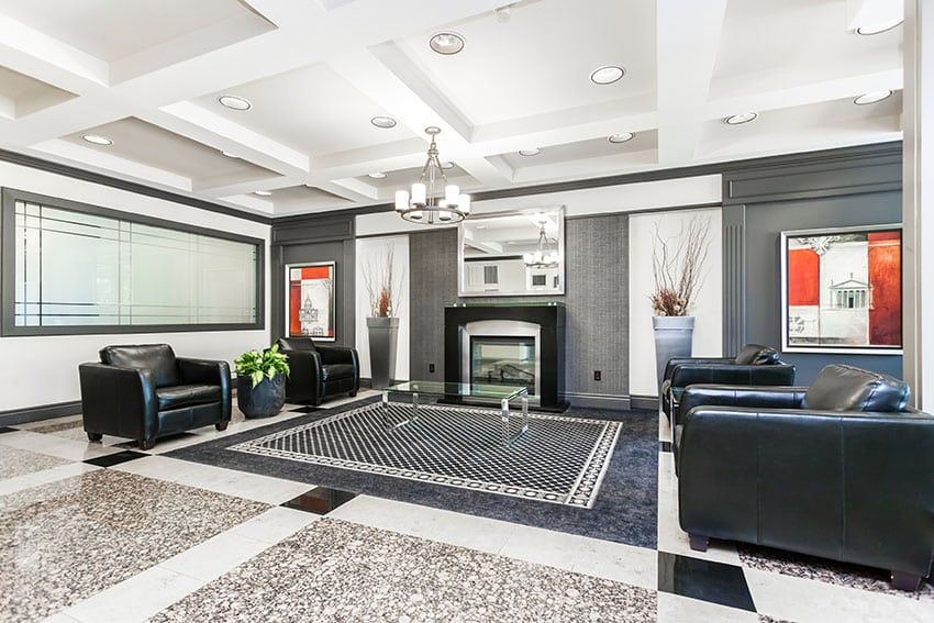 Contemporary living room design with black leather armchairs, modern fireplace and polished granite floors
