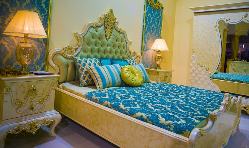 Elegant bedroom with decorative bed frame, tufted headboard and bright blue bedding