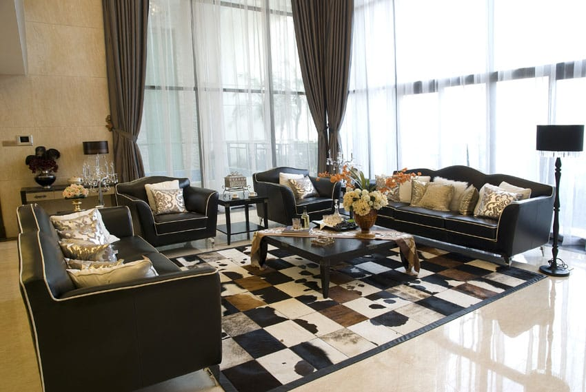 Elegantly furnished drawing room with high windows and dark furniture