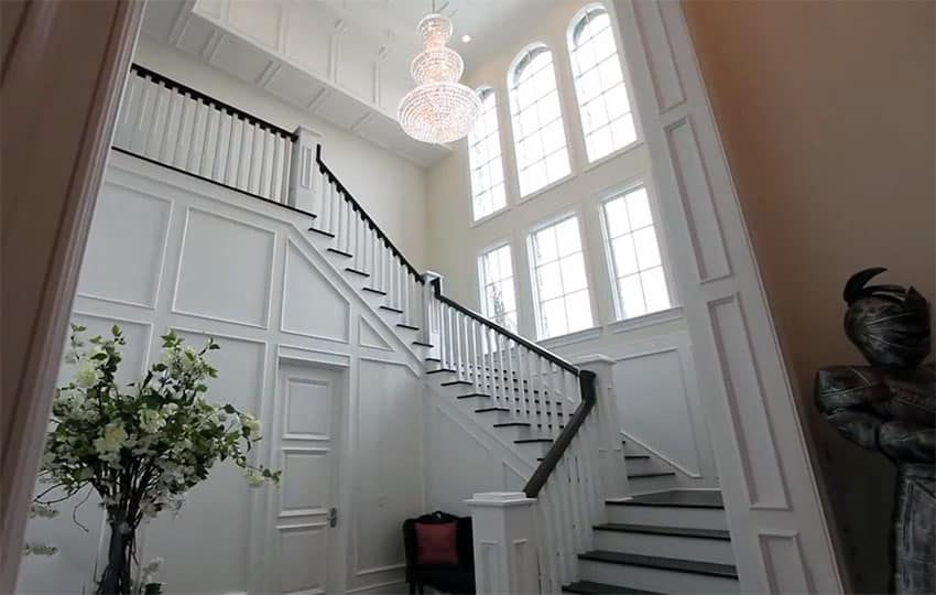 Grand white staircase with black railing at luxury estate home