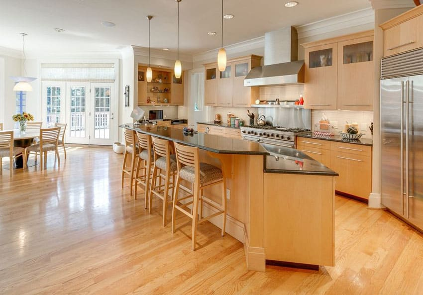 Kitchen with absolute black granite counter breakfast bar with honey color engineered hardwood floor