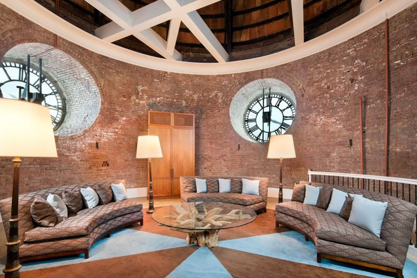 Large circular brick living room with round windows and three curved couches