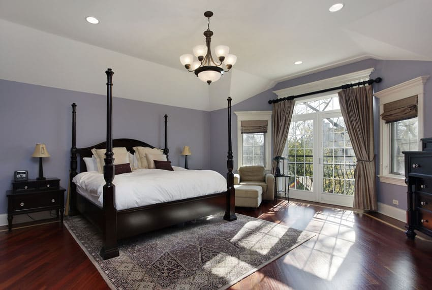 Large master bedroom with wood floors, purple walls and doors to balcony