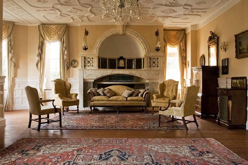 Large elegant formal living room with gold furniture decor and stone fireplace with custom mantle