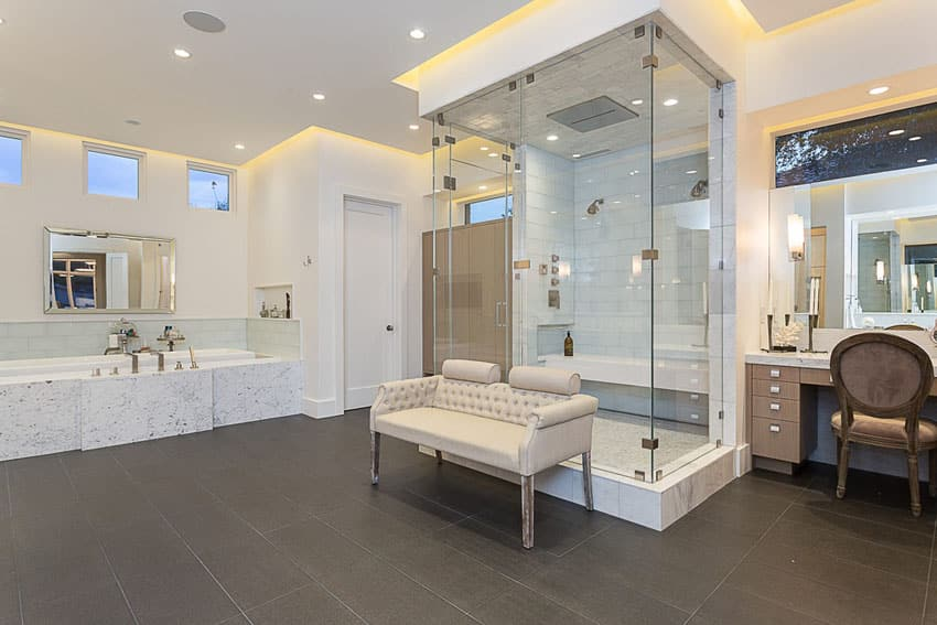 Beautiful master bathroom with large frameless shower in center of room and porcelain floor tile