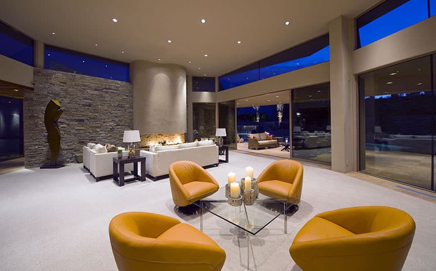 Large luxury living room with open floor plan, stacked stone wall and retractable patio door