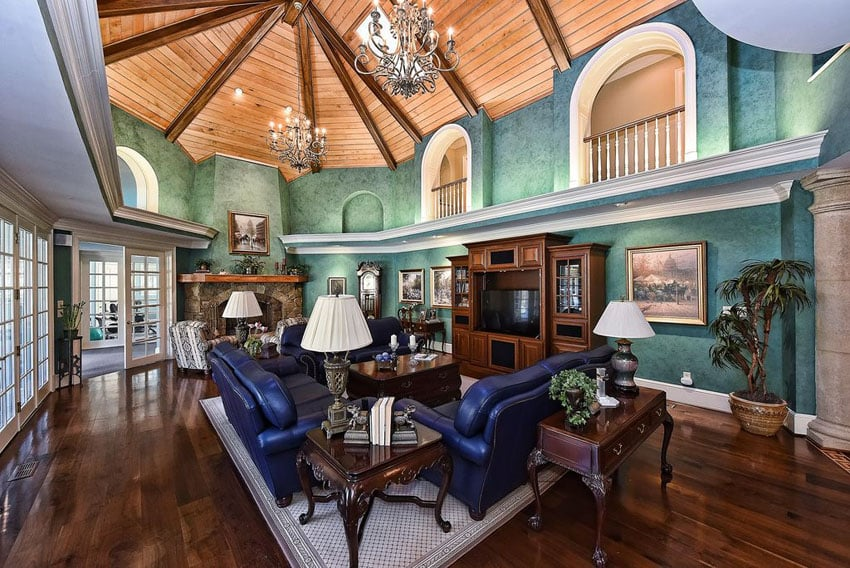 Large luxury living room with vaulted ceiling wood floors and blue furniture