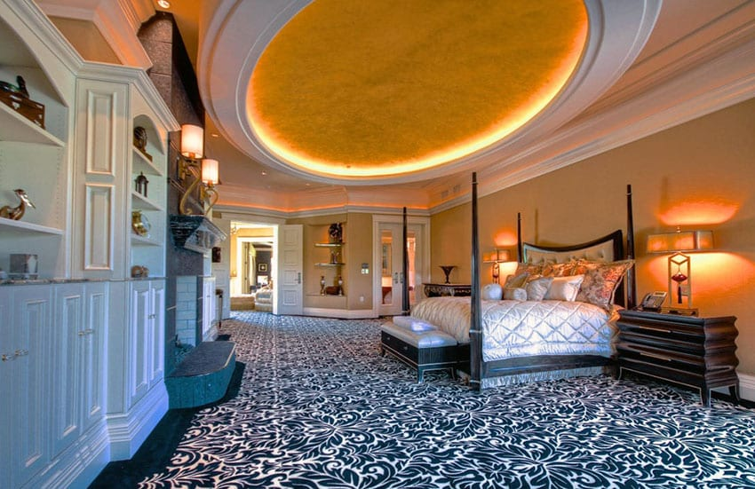 Large master bedroom in upscale home with circular ceiling feature, white built-ins, fireplace and patterned carpet