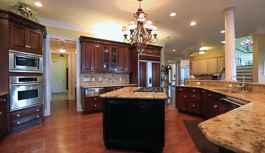 Large open kitchen with dark center island wood flooring and glass front cabinets