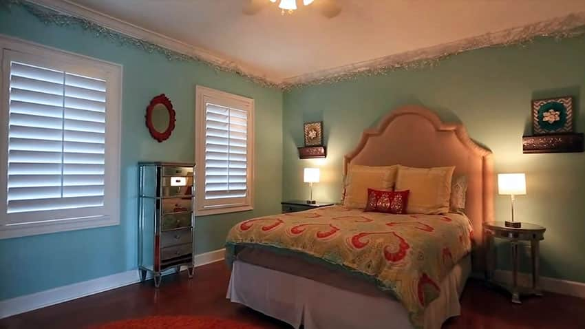 Light blue guest bedroom with plantation shutters