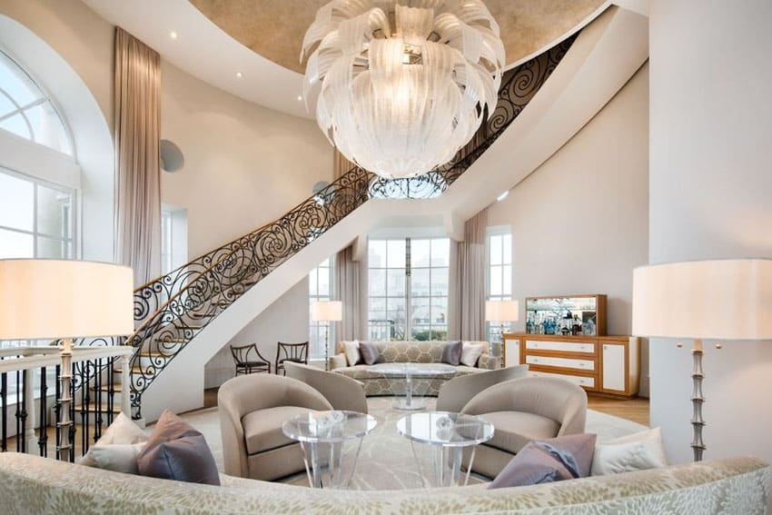 Living room with beautiful flowing flower style chandelier and wrought iron circular staircase