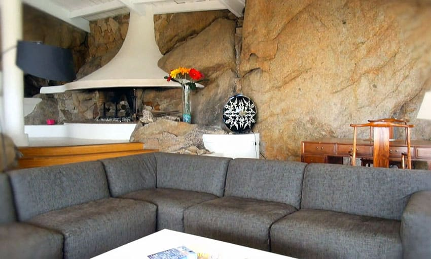 Living room with modern fireplace and solid rock wall