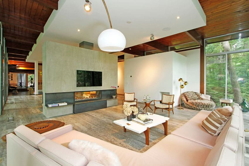 Living room with sandstone floors modern fireplace and globe light fixture