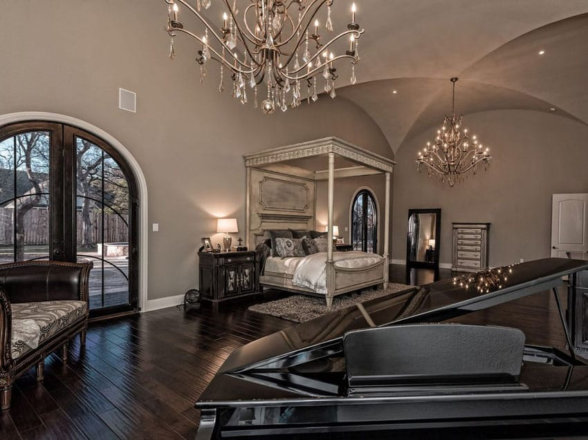 Luxury bedroom with four poster bed grand piano and two chandeliers