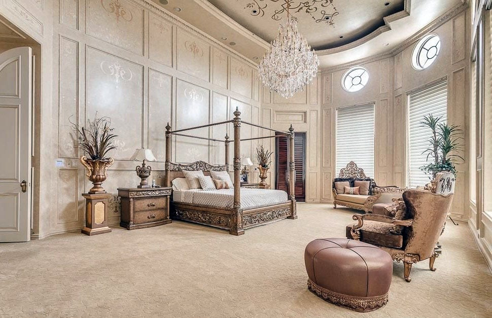 Luxury bedroom with spacious open layout, high ceilings, crystal chandelier and four post bed
