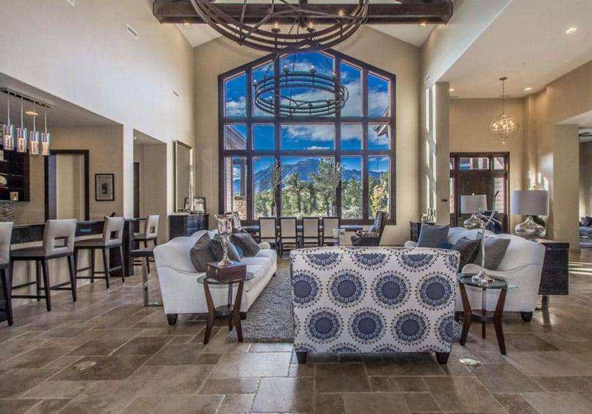 Luxury craftsman living room with wall of windows and large circular wrought iron chandeliers