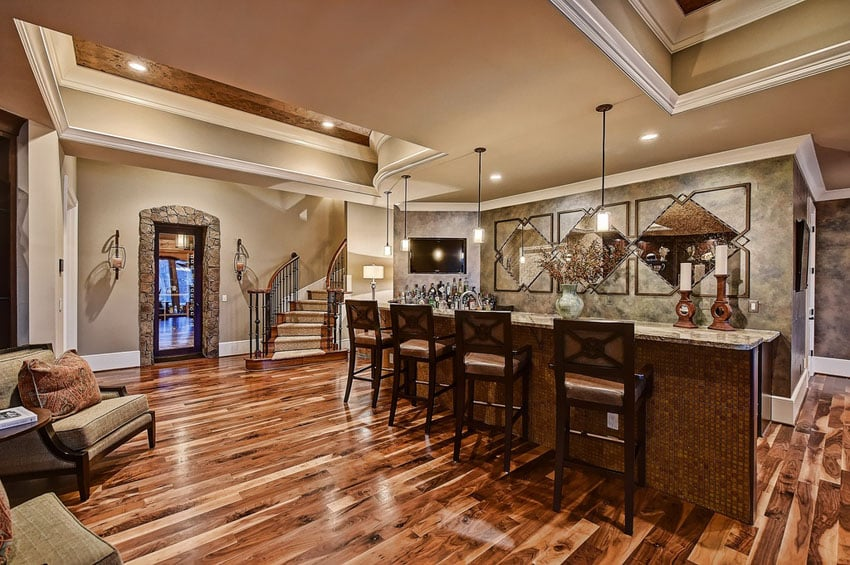 Luxury custom home bar with mosaic tile, pendant lights and hardwood floors