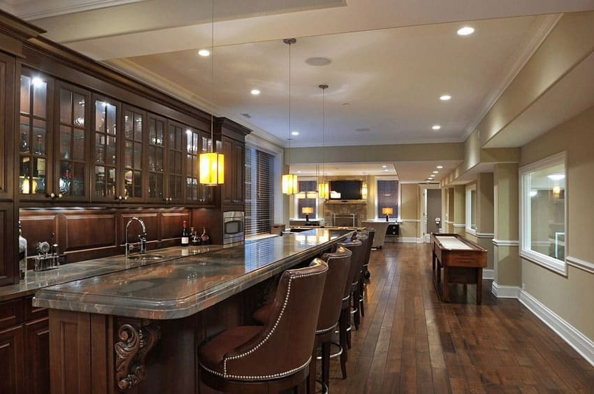 Luxury home bar with dark cabinetry and long granite counter