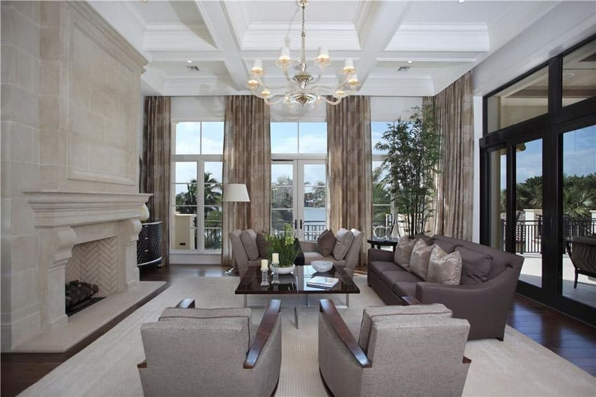 Luxury living room with corner layout with fireplace coffered ceiling and chandelier