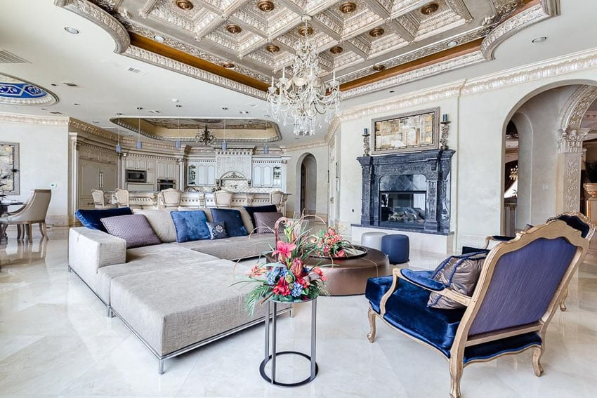 Luxury living room with high box ceiling, elegant chandelier, dark color fireplace and decorative molding