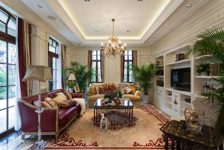 Luxury living room with large windows, polished marble floors, tray ceiling and bronze chandelier