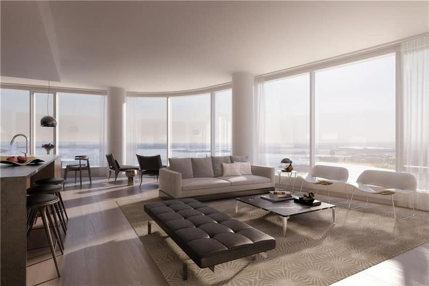 Luxury living room with muted design theme and wraparound window views of waterfront