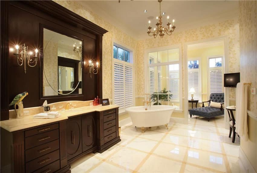 Luxury master bathroom with clawfoot tub with gold feet and marble flooring