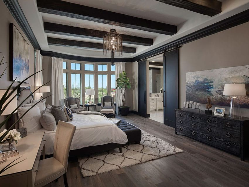 Luxury Mediterranean style bedroom with wide plank wood flooring and exposed wood beams