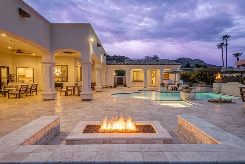 Luxury patio with stone bench seating around fire pit with pool views