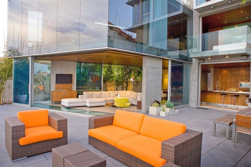 Luxury patio with synthetic rattan furniture with bright orange accent cushions