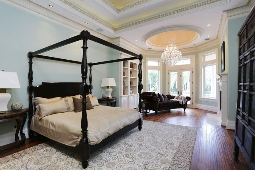 Luxury traditional master bedroom with four post bed chandelier and sitting area