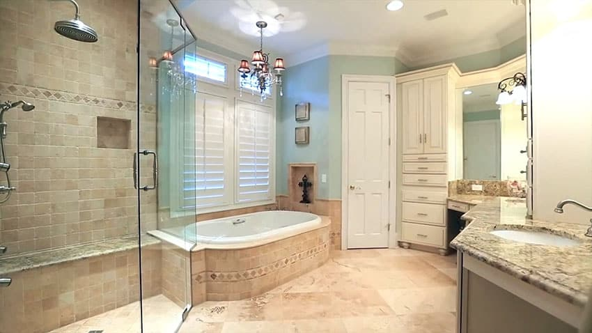 Master bathroom with limestone tile rainfall shower and bathtub surround