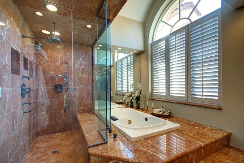 Master bathroom with red marble and rainfall shower with bathtub enclosure