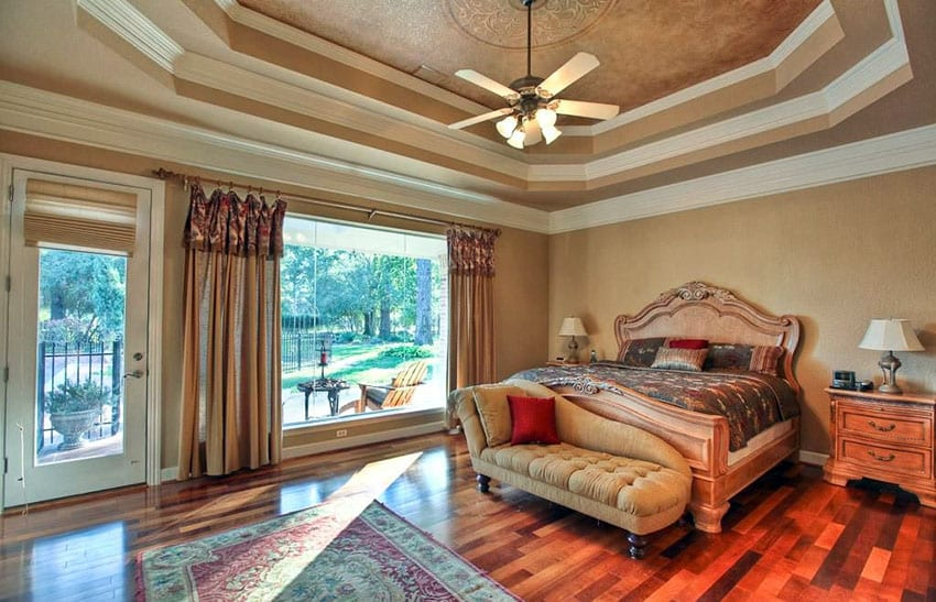 Master bedroom with tray ceiling, wood floors and large picture window with door to patio