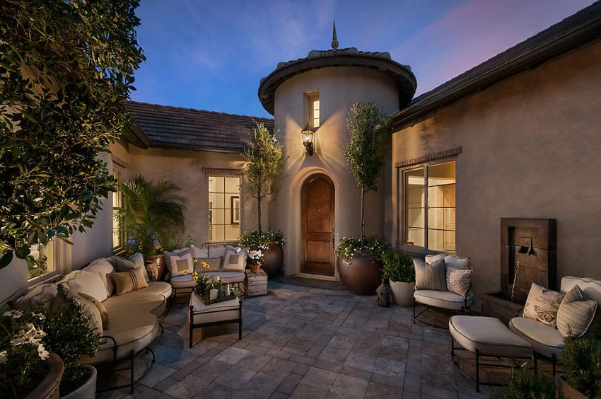 Mediterranean patio with comfortable outdoor seating and fountain