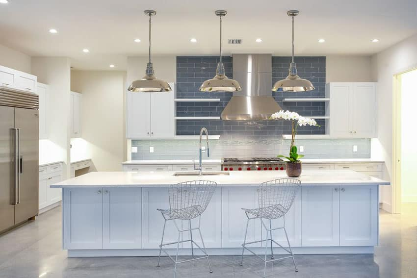 Modern beach style kitchen with polished concrete floors white cabinets and blue subway tile backsplash
