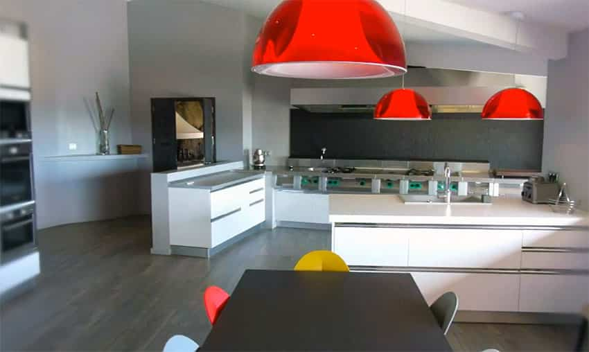 Modern kitchen with bright red lamps and white cabinets
