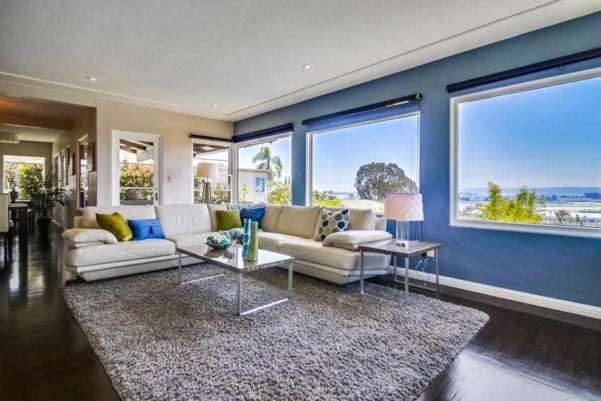 Modern living room with blue wall and picture window views of city