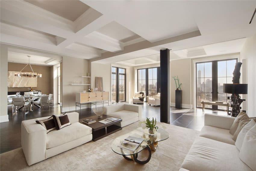 Modern living room with white furniture, herringbone style wood floors and city views