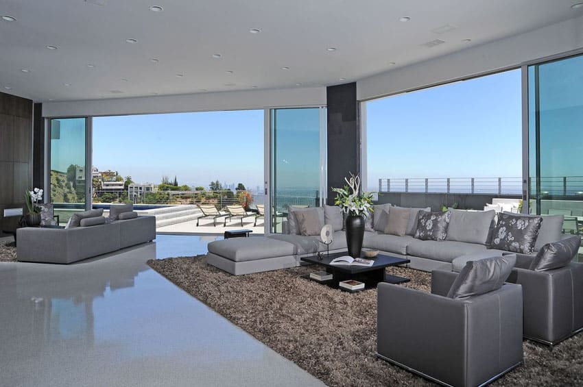 Open plan contemporary living room with gray furniture and expansive window views