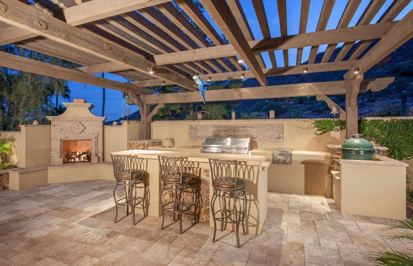 Patio with wood pergola covering outdoor kitchen next to fireplace