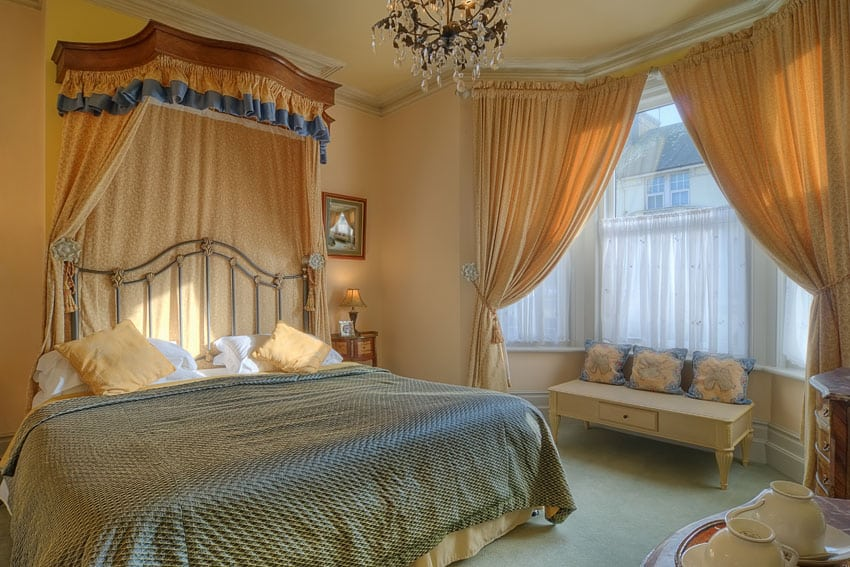 Pretty bedroom design with flowing curtains and glass chandelier