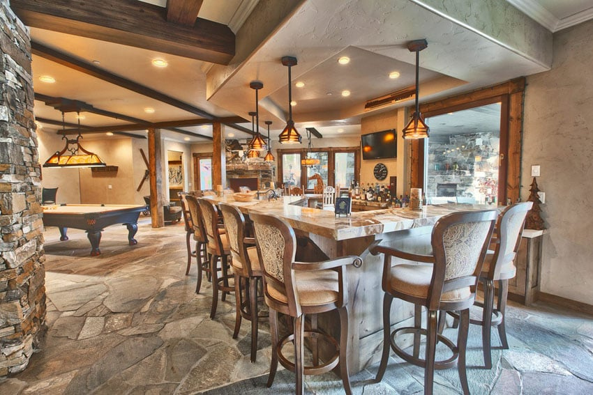 Rustic luxury home bar and game room with stone pillars and wood beams