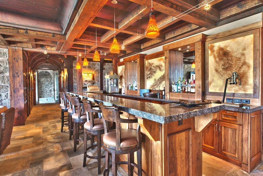 Rustic wood home bar with granite counters and tile flooring