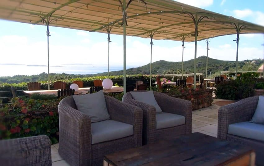 Synthetic rattan chairs on outdoor patio with ocean view