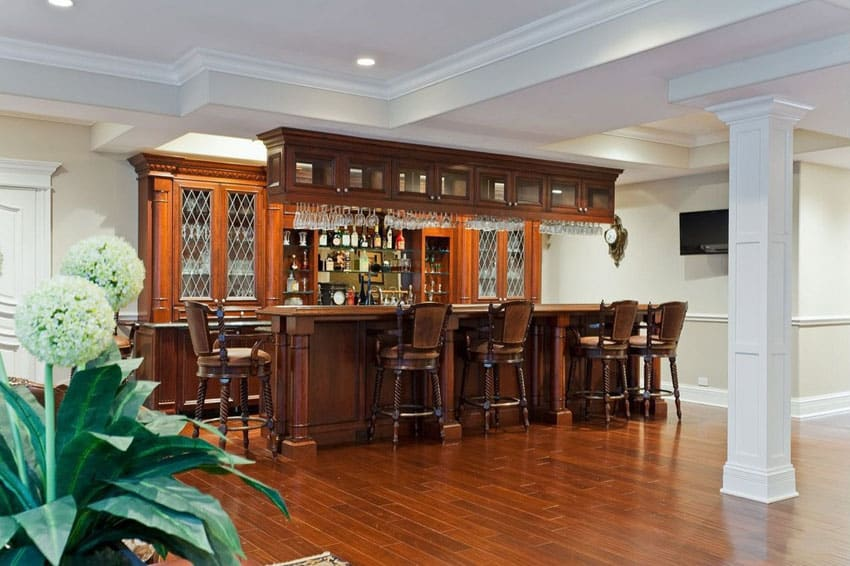 Traditional custom home bar with glass front cabinetry and teak wood floors