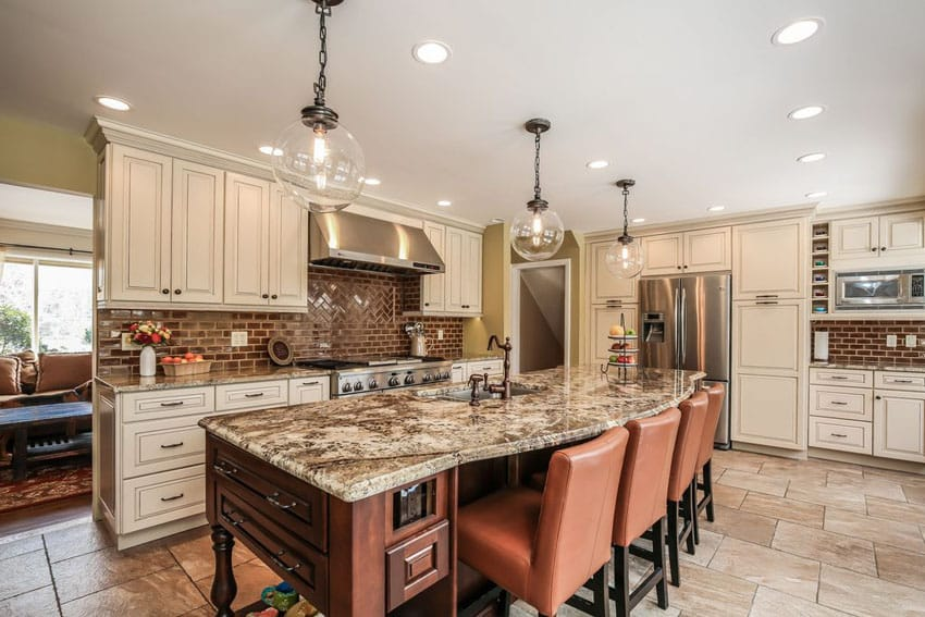Traditional kitchen with white cabinets brick backsplash and dining island