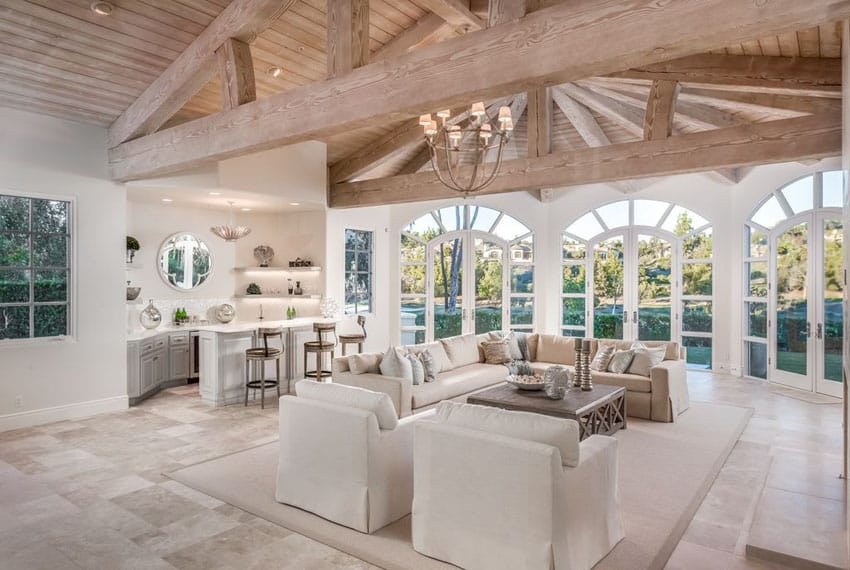 Traditional living room with cathedral ceiling limestone floors and home bar