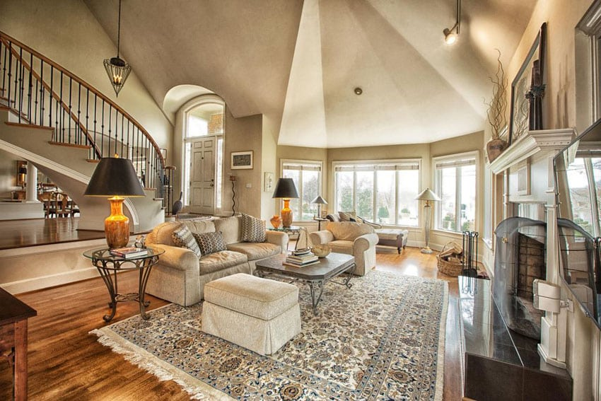 Traditional living room with wood floors, circular staircase and high ceiling